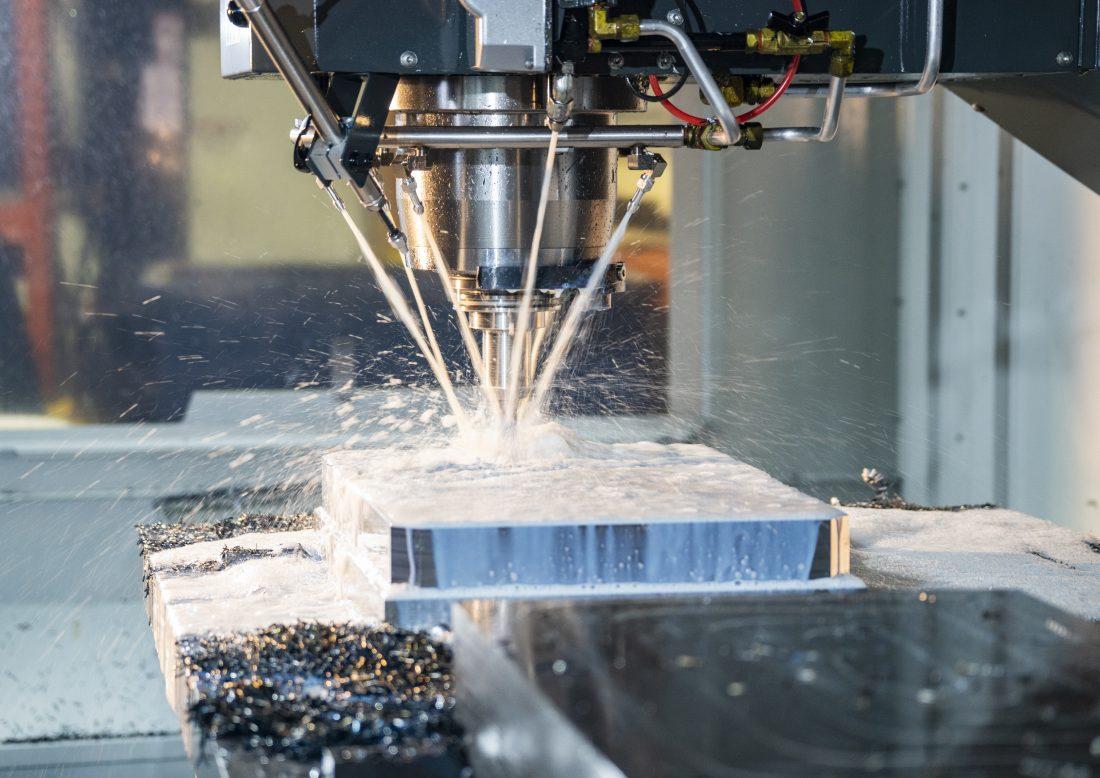 A modern CNC milling machine cutting steel in an industrial manufacturing machine shop.